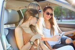 Las muchachas bastante europeas 25-30 años en el coche hacen la foto en el teléfono móvil Imagenes de archivo