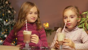 Las muchachas beben el chocolate caliente a través de una paja almacen de metraje de vídeo