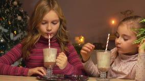 Las muchachas beben el chocolate caliente a través de una paja almacen de video