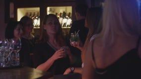 Las muchachas beben en el soporte de la barra en partido en club nocturno Sonrisa aclamación Gente Cóctel metrajes
