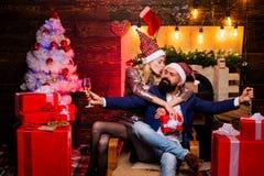 Las muchachas bebidas celebran Año Nuevo Mujer joven linda y hombre hermoso con el vestido de Papá Noel Tiempo de la Navidad para imagen de archivo