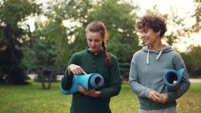 Las muchachas bonitas están caminando en el parque que sostiene las esteras de la yoga y que habla discutiendo el equipo de depor metrajes