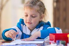 Las muchachas bonitas que se sientan en una tabla en el patio de la casa y dibujan el lápiz Foto de archivo libre de regalías