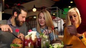 Las muchachas bonitas y el muchacho alegre que se sientan juntos en la tabla y est?n comiendo las hamburguesas almacen de metraje de vídeo