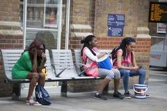 Las muchachas cansadas que recogieron el dinero para la caridad, se están sentando en un banco cerca de la estación de Liverpool  Fotos de archivo libres de regalías