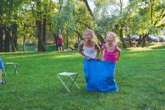 Las muchachas compiten en una raza de retransmisión Salto en bolsos Ríen y se caen Imágenes de archivo libres de regalías