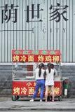 Las muchachas compran un bocado en un establo de la comida de la calle, Changchun, China Foto de archivo