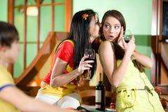 Las muchachas con el muchacho están bebiendo el vino rojo Foto de archivo libre de regalías