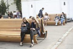 Las muchachas con el pelo largo se sientan en un banco de parque y miran el teléfono Fotos de archivo libres de regalías