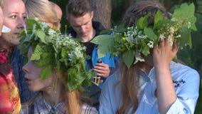 Las muchachas con las flores y las plantas coronan en el acontecimiento de la celebración del día de fiesta del pleno verano almacen de metraje de vídeo