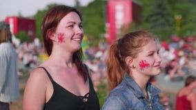 Las muchachas con la bandera de Gran Bretaña en mejillas miran el partido de fútbol en zona de la fan almacen de video