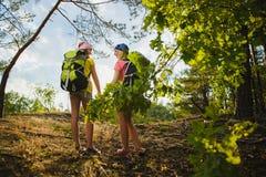 Las muchachas con la mochila en bosque de la colina se aventuran, viajan, concepto del turismo Imágenes de archivo libres de regalías