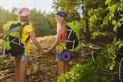 Las muchachas con la mochila en bosque de la colina se aventuran, viajan, concepto del turismo Imagen de archivo