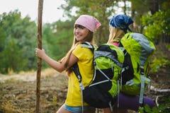 Las muchachas con la mochila en bosque de la colina se aventuran, viajan, concepto del turismo Foto de archivo libre de regalías
