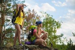 Las muchachas con la mochila en bosque de la colina se aventuran, viajan, concepto del turismo Fotografía de archivo