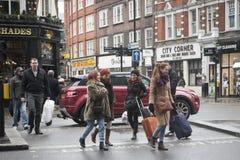 Las muchachas con las maletas que cruzan la calle cerca del nacional expresan la parada, donde usted puede llevar un autobús que  Foto de archivo