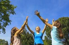 Las muchachas con las manos llevaron a cabo alto Imagen de archivo