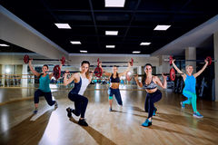Las muchachas con los barbells agrupan el entrenamiento en el gimnasio Imagen de archivo libre de regalías