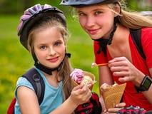 Las muchachas con verano del cono de helado de la consumición de la mochila de la bicicleta parquean Fotos de archivo