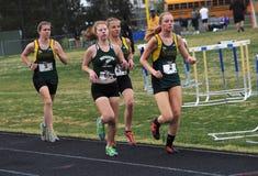 Las muchachas corren en una reunión de pista de la escuela secundaria imagenes de archivo