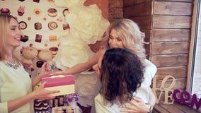 Las muchachas dan los regalos al amigo en honor del partido de Babyshower metrajes
