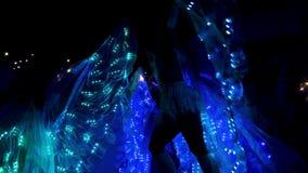 Las muchachas de la cámara lenta con las luces llevadas en los vestidos se realizan en la oscuridad almacen de video