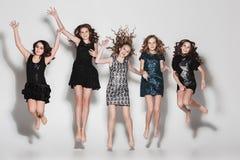 Las muchachas de la moda que saltan junto y que miran la cámara sobre fondo gris del estudio Fotografía de archivo libre de regalías