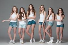 Las muchachas de la moda que se unen y que miran la cámara sobre fondo gris del estudio Foto de archivo