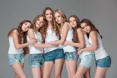 Las muchachas de la moda que se unen y que miran la cámara sobre fondo gris del estudio Fotos de archivo libres de regalías