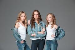 Las muchachas de la moda que se unen y que miran la cámara sobre fondo gris del estudio Imagen de archivo