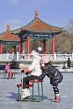 Las muchachas de la remolque se divierten en el hielo en el parque de Nanhu, Changchun, China Imagen de archivo