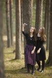 Las muchachas de los adolescentes hacen el teléfono del selfie en los amigos del bosque Fotografía de archivo libre de regalías