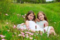 Las muchachas de los amigos de los niños en amapola de la primavera florecen el prado Imagen de archivo libre de regalías