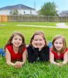 Las muchachas de los niños agrupan la mentira en la sonrisa de la hierba del césped feliz Imagenes de archivo