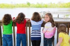 Las muchachas de los niños apoyan la mirada del lago en la verja Imagenes de archivo