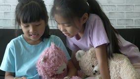 Las muchachas de los niños asiáticos que leen una historia en sala de estar en casa almacen de metraje de vídeo