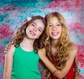 Las muchachas de los niños hermosos de los amigos abrazan junta la sonrisa feliz Foto de archivo