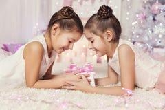 Las muchachas de los niños abren el regalo del presente de cumpleaños, dos niños Foto de archivo libre de regalías