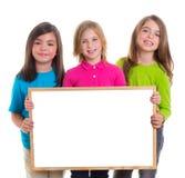 Las muchachas de los niños agrupan llevar a cabo el espacio en blanco de la copia de la tarjeta blanca Fotos de archivo libres de regalías