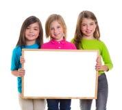 Las muchachas de los niños agrupan llevar a cabo el espacio en blanco de la copia de la tarjeta blanca Imagen de archivo libre de regalías