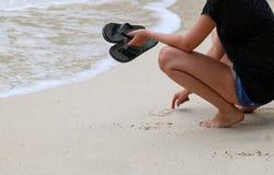 Las muchachas de los turistas que llevan las sandalias gozan de las playas y de la agua de mar Imagen de archivo
