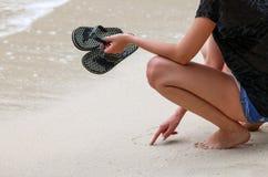 Las muchachas de los turistas que llevan las sandalias o el deslizador gozan de la playa Fotos de archivo libres de regalías