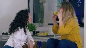 Las muchachas del chisme con las manzanas en manos hablan el uno al otro en el ocio almacen de video