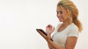 Las muchachas del mulato están mecanografiando usando la tableta almacen de metraje de vídeo