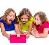 Las muchachas del niño de las hermanas con tecnología hacen tabletas jugar de la PC feliz Imagen de archivo libre de regalías