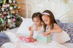 Las muchachas del niño despiertan en su cama por mañana de la Navidad Imagen de archivo libre de regalías