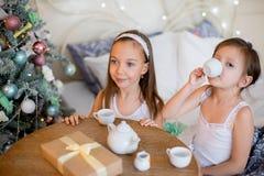 Las muchachas del niño despiertan en su cama por mañana de la Navidad Foto de archivo libre de regalías