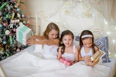 Las muchachas del niño despiertan en su cama por mañana de la Navidad Fotos de archivo libres de regalías
