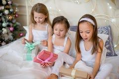 Las muchachas del niño despiertan en su cama por mañana de la Navidad Foto de archivo