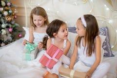 Las muchachas del niño despiertan en su cama por mañana de la Navidad Fotografía de archivo libre de regalías